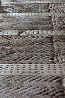 The brick flooring of the stalls, laid in a herringbone pattern, reveals how the bricks have worn under the horses' hooves over the years