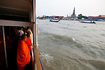 Chao Phraya River, Bangkok, Thailand. Monks looking at Wat Arun from the Orange Flag Express Boat