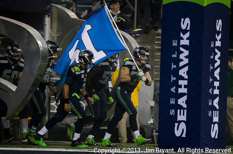 Seattle Seahawks linebacker Heath Farwell carries the 12th Man Flag as the team runs out onto the field before their game against the New Orleans Saints at CenturyLink Field in Seattle, Washington on December 2, 2013. The Seahawks beat the Saints 34-7 to take the best record team in the NFL.©2013. Jim Bryant Photo. ALL RIGHTS RESERVED.