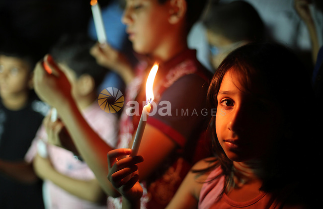 Palestinian children hold candles in a protest to show solidarity with Palestinian prisoner Bilal Kayed, who has been fasting for almost two months over his detention without trial, in Gaza seaport, on August 18, 2016. Kayed was to be released in June after serving a 14-and-a-half-year sentence for activities in the leftist Popular Front for the Liberation of Palestine (PFLP), labelled a terrorist organisation by Israel, the European Union and the United States. Instead, Israeli authorities ordered that he remain in custody under the administrative detention law, which allows prisoners to be held without trial for renewable six-month periods. Photo by Mohammed Asad