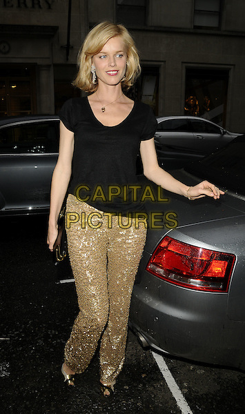 EVA HERZIGOVA.Flagship store launch party, Michael Kors boutique, London, England..April 27th, 2009.full length black top gold sequins sequined trousers peep toe shoes clutch bag hand.CAP/CAN.©Can Nguyen/Capital Pictures.