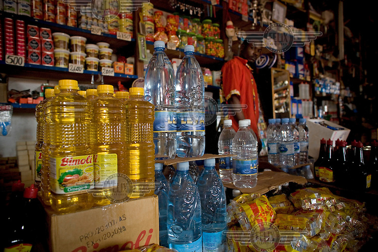 In front of shelves of food a shop worker stands behind the counter where cooking oil and bottled water are being displayed for sale.