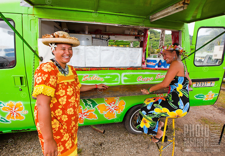 Two Tahitian women in floral dresses at Le Truck lunch truck