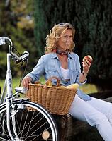 junge Frau mit Fahrrad und Einkaufskorb bei einer Rast, isst einen Apfel | young woman with bicycle and shopping basket having a break, eating an apple