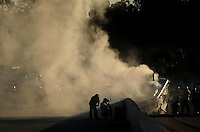 Nov 12, 2010; Pomona, CA, USA; NHRA  safety personnel work to extinguish the fire on the funny car driven by Tim Wilkerson after he exploded an engine during qualifying for the Auto Club Finals at Auto Club Raceway at Pomona. Mandatory Credit: Mark J. Rebilas-