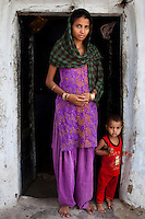 Sadma Khan, 19, poses with her 18 month old son for a portrait at the door of her mother's one-room house in a slum area of Tonk, Rajasthan, India, on 19th June 2012. She was married at 17 years old to Waseem Khan, also underaged at the time of their wedding. The couple have an 18 month old baby and Sadma is now 3 months pregnant with her 2nd child and plans to use contraceptives after this pregnancy. She lives with her mother since Waseem works in another district and she can't take care of her children on her own. Photo by Suzanne Lee for Save The Children UK