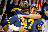 Michigan Wolverines outfielder Jordan Brewer (22) hugs teammate Tommy Henry (47) after his complete game shutout in Game 6 of the NCAA College World Series against the Florida State Seminoles on June 17, 2019 at TD Ameritrade Park in Omaha, Nebraska. Michigan defeated Florida State 2-0. (Andrew Woolley/Four Seam Images)