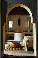 A view through a Moorish arch to a double bedroom beyond where two washbasins and a bath are set on a raised platform to one side of the double bed.
