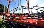 NIGTEVECHT - Langs het Amsterdam-Rijnkanaal in Nigtevecht wordt de boog van de nieuwe door bouwcombinatie KWS-Mercon gebouwde en door Movares ontworpen Loenerslootsebrug met kranen op het brugdek vastgezet. De grotendeels in de fabriek in Gorinchem opgebouwde stalen boogbrug is één van de nieuwe bruggen die in opdracht van Rijkswaterstaat gebouwd wordt ter vervanging van verouderde bruggen en ter verhoging van de doorvaarthoogte voor vierlaagse containerschepen. Vanaf deze tijdelijk bouwlocatie wordt de brug verder afgebouwd en binnenkort naar zijn nieuwe bestemming worden gevaren om de plaats van de huidige - te verwijderen - Loenenslootse in te nemen. COPYRIGHT TON BORSBOOM