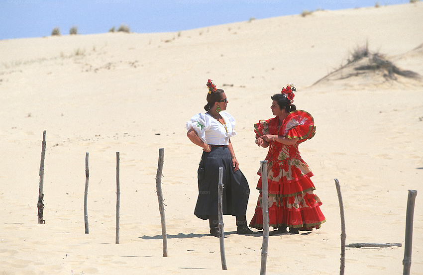 "Women in flamenco dresses in the sand dunes. The pilgrim route of the Hermandade de Sanlucar de Barrameda from Sanlucar across the Parque Donana to El Rocio, Huelva Province, Andalusia, Spain...El Rocio follows on from Semana Santa - Easter week and the various spring ferias, of which Seville's Feria de Abril (April) is the biggest. The processions to the (Hermitage) Hermita de El Rocío, at Pentecost, is the most famous (Romeria) pilgrimage in the Andalusian region, attracting nearly a million people from across Andalusia, Spain and the world. The cult started off in the 13th century when a statue of the virgin Mary was apparently found in a tree trunk in the Donana Park. What was first a local devotion at Pentecost by local pilgrim brotherhoods ""hermandades"" became by the 19th century into dozens of fraternities developed from such as Cadiz, Selville and Huelva. Some walk for several days, others travel with oxen drawn wagons or on horseback, with traction engines and all terrain vehicles, camping along the trail they take. They wear Andalusian costumes, tight breeches, boots, short jackets and frilly flamenco skirts. Many festivities, flamenco dance, laments, songs and music are combined with religious prayers. Devout pilgrims walk as a penance, keeping vows of silence. An emblem of the immaculate conception (sin peche) is carried. On the Pentecost after the stroke of midnight on the whit Sunday the virgin Mary is carried from the church through the streets of El Rocio by each hermandade to visit each brotherhood's shrine."