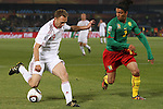 19 JUN 2010: Dennis Rommedahl (DEN) (19) and Benoit Assou-Ekotto (CMR) (2). The Denmark National Team defeated the Cameroon National Team 2-1 at Loftus Versfeld Stadium in Tshwane/Pretoria, South Africa in a 2010 FIFA World Cup Group E match.