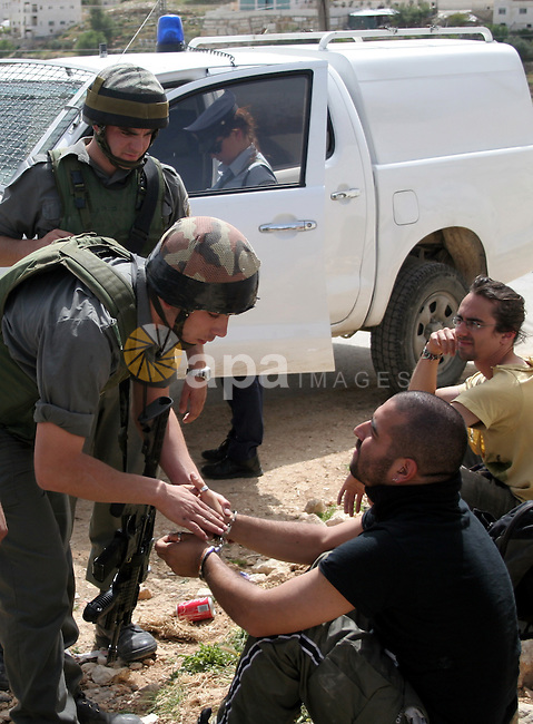 Israeli soldiers detain an International activist during a rally against Israel's separation barrier in the West Bank village of al-Masarah near Bethlehem, April 02, 2010. Israel says the barrier is needed for security, but Palestinians think of it as a land grab that undermines their promised state. Photo by Najeh Hashlamoun