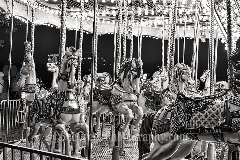 This is an image of the carousel horses at a amusement fair taken late at night after the last ride of the night in black and white which brings out that sort of haunting errie look almost like something a little surreal or somenthing you would see in a  a twilight zone episode .
