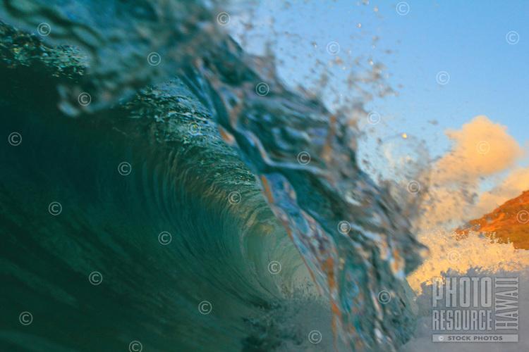 A small tube breaks at sunrise at Sandy Beach, O'ahu.