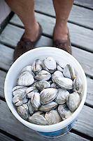 Ocracoke fisherman, James Barrie Gaskill, delivers his catch of the day (clams) to Ruth Toth.