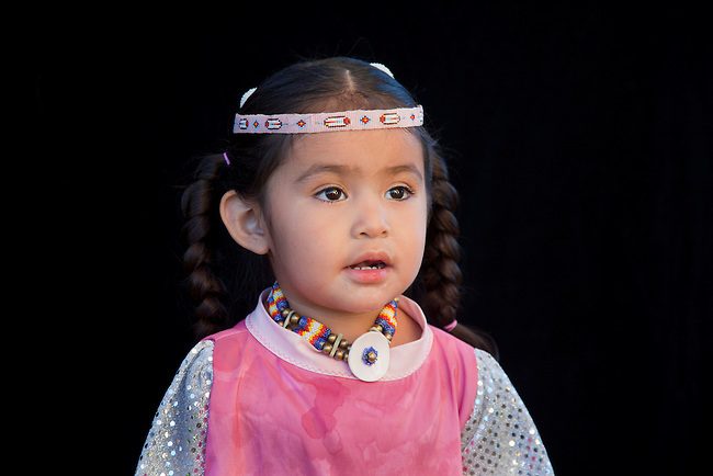 2 year old Lillia Baker (Shoshone-Bannock) dressed in beaded headband and choker with braids on black background