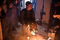 SYRIA: A YPJ fighter heats up around a fire at the rear base of the front line of the cement plant located 6 km from the town of Tal Abyad.<br /> <br /> SYRIA: Une combattante YPJ se réchauffe autour d'un feu à la base arrière de la ligne de front de la cimenterie située à 6 km de la ville de Tal Abyad.