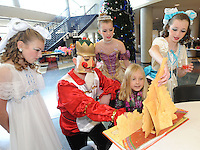 STAFF PHOTO ANDY SHUPE - James Miskimen of Rogers, center; Emma Ronck, 10, left; Abby Ryals, 12, top; and Hannah Campbell, 12, right; show Teagan Schuckman, 9, of Rogers a fold-out book about The Nutcracker ballet during the Sugar Plum Tea Party Sunday, Dec. 7, 2014, at Rogers High School. The Ballet Westside Performing Company in Rogers hosted the event prior to their second performance of The Nutcracker in the school's performing arts center. Members of the cast spent time interacting with visitors and served cake and cookies.