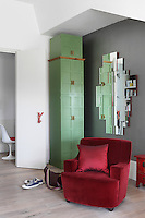 The rich red colour of the armchair combined with the tall green cupboards gives this area of the living room an Oriental feel