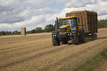 Yellow tractor carrying load of straw bales across field of stubble, Sutton, Suffolk, England