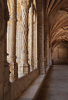 Arcade of the Cloister, with intricately carved columns and a rib vaulted ceiling with decorative bosses, built in Manueline style by Diogo Boitac, Joao de Castilho and Diogo de Torralva, completed 1541, in the Jeronimos Monastery or Hieronymites Monastery, a monastery of the Order of St Jerome, built in the 16th century in Late Gothic Manueline style, Belem, Lisbon, Portugal. The cloister wings have wide arcades with rectangular column and tracery within the arches. The monastery is listed as a UNESCO World Heritage Site. Picture by Manuel Cohen