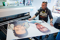 """6th April 2020, North Rhine-Westphalia, Germany;  The first """"cardboard comrades"""" - fans of Borussia Mönchengladbach - who come out of the printer are controlled by Thomas Heyer, an employee of a printing company. The fans of Borussia Mönchengladbach want to contribute to a better mood at possible ghost games in the German Soccer League. In order to spare TV viewers and professionals a view of the empty stadium seats, cardboard figures showing the likeness of the supporters are to be set up life-size - if desired, where the spectators stand or sit during normal games."""