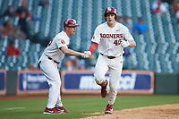 Brady Lindsly (40) of the Oklahoma Sooners shakes hands with third base coach Clay Van Hook after hitting a home run against the Arkansas Razorbacks in game two of the 2020 Shriners Hospitals for Children College Classic at Minute Maid Park on February 28, 2020 in Houston, Texas. The Sooners defeated the Razorbacks 6-3. (Brian Westerholt/Four Seam Images)