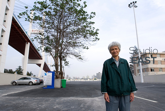 68-year-old Shi Yuji poses for a photograph in front of the place where her house was destroyed to make way to a parking lot for Shanghai World Expo 2010, under Nanpu bridge, in Shanghai, China, on May 12, 2010. Shi Yuji's house has been destroyed on April 10. She now lives in a workers' dormitory. Photo by Lucas Schifres/Pictobank