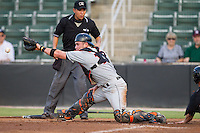 Delmarva Shorebirds catcher Austin Wynns (12) stretches for a throw at home plate as umpire Takahito Matsuda looks on during the game against the Kannapolis Intimidators at CMC-NorthEast Stadium on July 2, 2014 in Kannapolis, North Carolina.  The Intimidators defeated the Shorebirds 6-4. (Brian Westerholt/Four Seam Images)