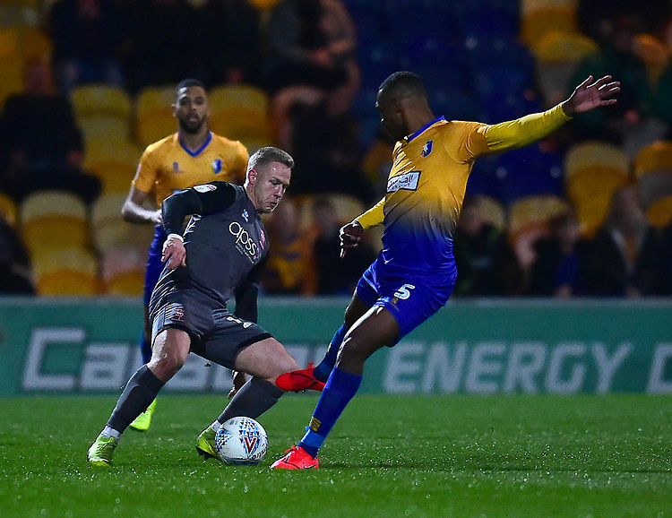 Lincoln City's Danny Rowe vies for possession with Mansfield Town's Krystian Pearce<br /> <br /> Photographer Andrew Vaughan/CameraSport<br /> <br /> The EFL Sky Bet League Two - Mansfield Town v Lincoln City - Monday 18th March 2019 - Field Mill - Mansfield<br /> <br /> World Copyright © 2019 CameraSport. All rights reserved. 43 Linden Ave. Countesthorpe. Leicester. England. LE8 5PG - Tel: +44 (0) 116 277 4147 - admin@camerasport.com - www.camerasport.com