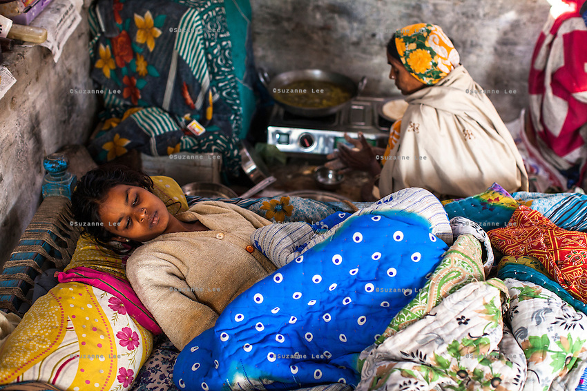 Meera lies in bed as her mother makes breakfast in their shelter where the family live and work as earring makers in Varanasi, Uttar Pradesh, India on 19 November 2013.