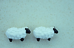 Two nearly identical china models of sheep hand-painted white and black following each other with antique paper background