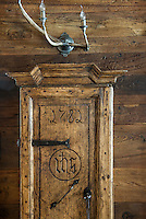 Detail of a cupboard in the living room, its marked and worn surface blending with the rough patina of the wood cladding behind