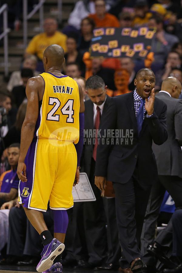 Jan. 30, 2013; Phoenix, AZ, USA: Los Angeles Lakers guard Kobe Bryant (24) walks past Phoenix Suns interim head coach Lindsey Hunter at the US Airways Center. Mandatory Credit: Mark J. Rebilas-