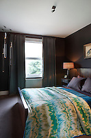 The guest bedroom painted in a rich chocolate brown was initially an experiment in redecoration and has resulted in an cosy space furnished with carefully chosen bed linen and contemporary light fittings