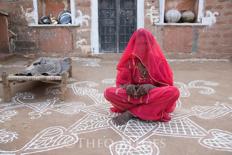 Rajasthani woman sitting in yard in front of her more sophisticated stone house; most houses in the rural areas of Rajasthan are built out of clay and dung, Rajasthan, India --- Model Released