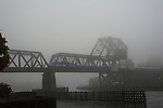 Fog along the Lake Washington Ship Canal. Ballard Railroad Trestle at West end of Chittenden lock. The Sounder heading North into Seattle.