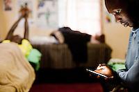 Kenyan marathon runner Wilson Kipsang checks his phone while Abel Kirui waits for a massage in the  Physio room of the Demadonna camp in Iten, Kenya.