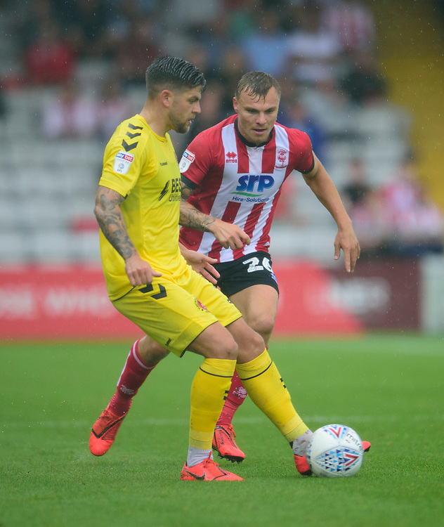 Fleetwood Town's Danny Andrew under pressure from  Lincoln City's Harry Anderson<br /> <br /> Photographer Andrew Vaughan/CameraSport<br /> <br /> The EFL Sky Bet League One - Lincoln City v Fleetwood Town - Saturday 31st August 2019 - Sincil Bank - Lincoln<br /> <br /> World Copyright © 2019 CameraSport. All rights reserved. 43 Linden Ave. Countesthorpe. Leicester. England. LE8 5PG - Tel: +44 (0) 116 277 4147 - admin@camerasport.com - www.camerasport.com
