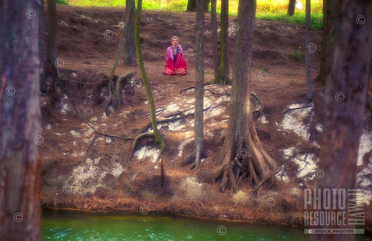 Woman meditating near stream, Waimanalo, Oahu