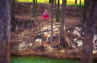 Woman meditating near stream, Waimanalo, Oahu