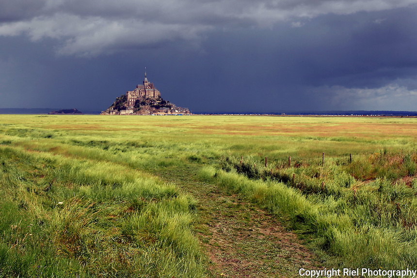 A view from a pasture of the tidal island of Le Mont Saint-Michel with a stormy skyline. The island has held strategic fortifications since ancient times, and since the 8th century AD been the seat of the monastery from which it draws its name. Mont Saint-Michel and its bay are part of the UNESCO list of World Heritage Sites. More than 3,000,000 people visit it each year.