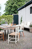 Mismatched chairs surround the garden table which is made from salvaged materials