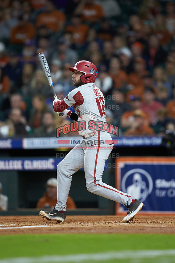 Casey Opitz (12) of the Arkansas Razorbacks follows through on his swing against the Texas Longhorns in game six of the 2020 Shriners Hospitals for Children College Classic at Minute Maid Park on February 28, 2020 in Houston, Texas. The Longhorns defeated the Razorbacks 8-7. (Brian Westerholt/Four Seam Images)