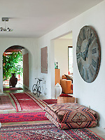 A collection of rugs covers the floor to the entrance hall of this contemporary house, which has a massive clock face dominating one wall
