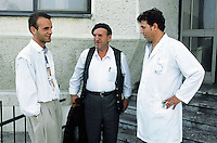 Kosovo. Pristina. University hospital. Dr Bujar Berisha ( first from the right) talks to a father and his son who just finished a therapeutic treatment on heroin addiction.  © 2001 Didier Ruef