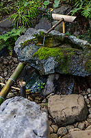 Shishi odoshi or deer scare is a gereric device made to scare away animals such as deer from damaging gardens and even a farm.  Sozu is a special water fountain used specifically in Japanese gardens.  Sozu consists of a bamboo tube pivoted to its balance point - its heavier end is down and resting against a rock while water fills into the other end of the bamboo tube.  After the water has accumulated this moves the tube's center of gravity past the pivot, causing the tube to rotate and release water. The heavier end falls back against the rock making a sharp sound, and the cycle repeats. This noise is intended to startle deer which may be grazing on plants in the garden.