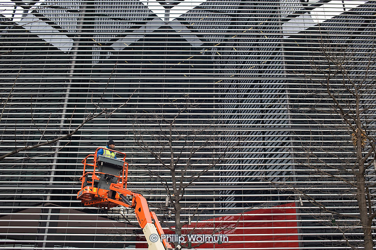 A workmen removes Christmas lights from trees outside 6 More London Place, close to City Hall on the south bank of the Thames.