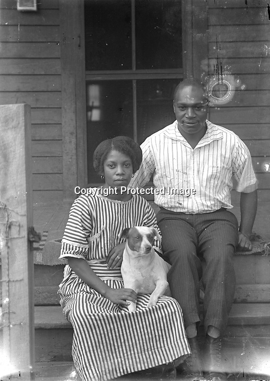 ON THE FRONT STEPS. The fence post at left indicates this portrait was snapped through the open gateway of a shallow front yard. The identity of the young couple has not been discovered (SEE BELOW), but their comfortable closeness and her casual display of a ring on her left hand suggests they are married. The family dog does not appear to be an entirely willing participant, but the couple is cooperating in gentle restraint.<br />