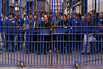 Barrow in Furness, Cumbria. 1980's<br /> At the end of their shift, workers at Vickers Shipbuilding and Engineering, Ltd gather behind the chained and padlocked factory gates waiting for the shipyards whistle to sound, denoting the end of their working day. It's time to go home.